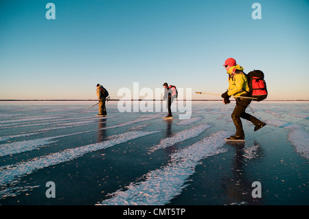Three people ice skating - Stock Photo