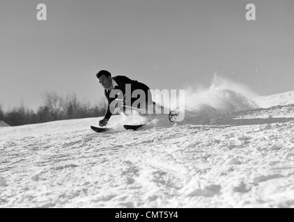 1940s MAN SKIING DOWNHILL RACING FAST SNOW FLYING WINTER OUTDOOR - Stock Photo