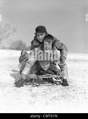1950s THREE BOYS PILED ON TOP OF SLED ON SNOW COVERED HILL OUTDOOR LOOKING AT CAMERA - Stock Photo