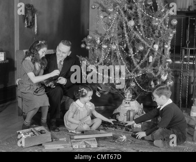 1930s FATHER AND SON PLAYING WITH CHRISTMAS TOY TRAIN SET Stock ...