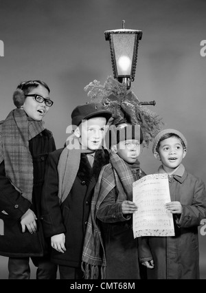 1960s FOUR MULTI ETHNIC BOYS GROUP SINGING CHRISTMAS CAROL TOGETHER STANDING BY OUTDOOR PORCH LIGHT - Stock Photo