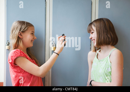 Girl showing something to her friend on mobile phone - Stock Photo