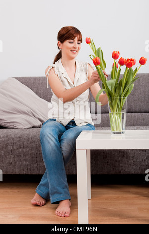 Beautiful young woman at home making an arrangement of orange tulips - Stock Photo