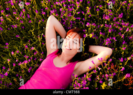 Top view of a beautiful young woman lying on a flowery meadow - Stock Photo