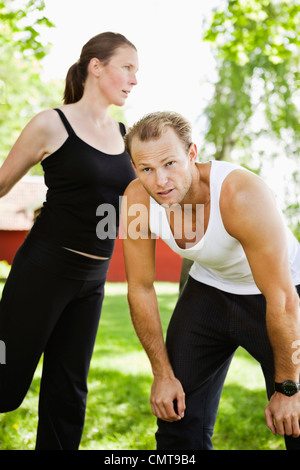 Woman exercising while leaning on tired man - Stock Photo