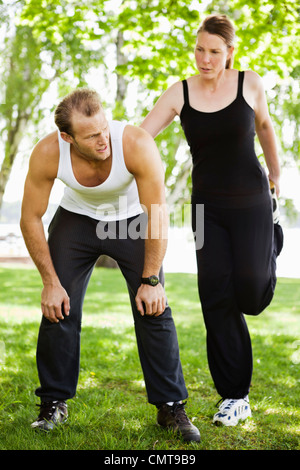 Woman leaning on tired man and exercising - Stock Photo