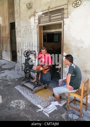 A middle aged Cuban shoe repairman repairs a shoe while his customer sits and waits in Havana, Cuba. - Stock Photo