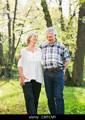 Senior couple walking in woods - Stock Photo