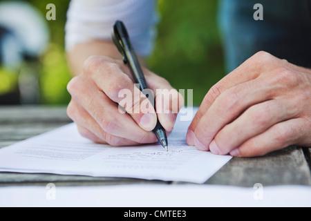 Man writing on paper - Stock Photo