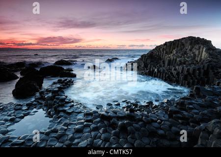 sunset sky skies over the hexagonal shaped basalt columns Giant's Causeway County Antrim Northern Ireland - Stock Photo