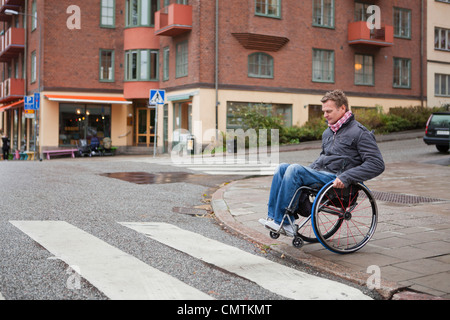Man in wheelchair crossing road - Stock Photo