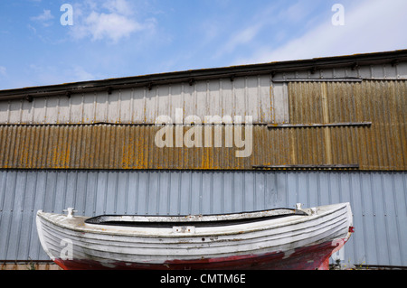 Small boat in front of large store-house - Stock Photo