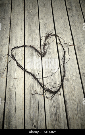 Lace lying on a wooden deck formed as a heart - Stock Photo