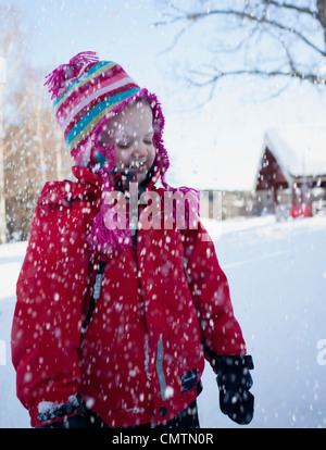 Girl (6-7) standing in snow fall - Stock Photo