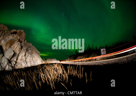 Lights of a passing vehicles under Aurora Borealis at the start of the Ingraham Trail, outside Yellowknife, NWT - Stock Photo