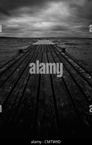 Close-up of pier with horizon over water - Stock Photo