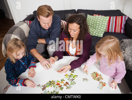 Parents and children (2-4) playing puzzle game - Stock Photo