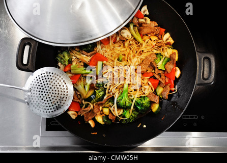 Cooking vegetable stir-fry in a wok - Stock Photo
