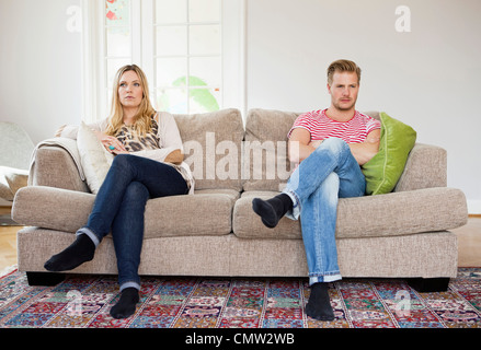 Couple looking away while sitting on sofa with arms folded - Stock Photo