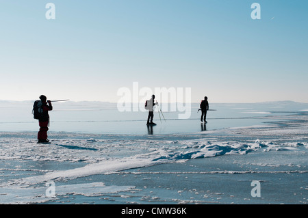 Three people on the ice against sky - Stock Photo