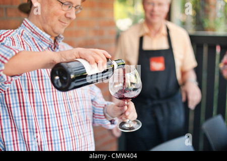 Mature man pouring wine in glass - Stock Photo