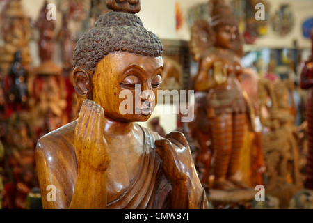 Sri Lanka - traditional wood carving, shop with wooden souvenirs, detail of buddha statue - Stock Photo
