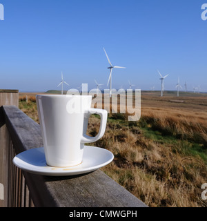 A mug of tea on a saucer sitting on a handrail with Whitelee windfarm in the background. Concept. - Stock Photo