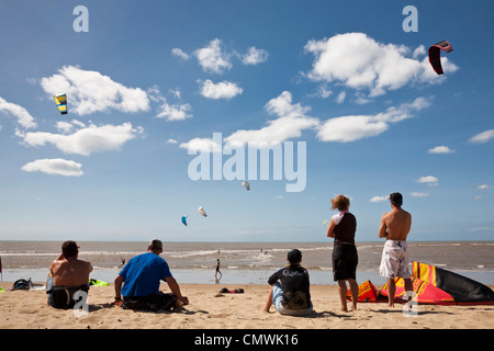 Group watching kite-surfers at Yorkeys Knob beach. Cairns, Queensland, Australia - Stock Photo