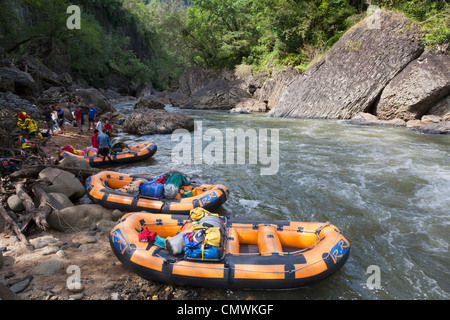 Rafts on riverbank during white-water rafting expedition on North Johnstone River, Queensland, Australia - Stock Photo