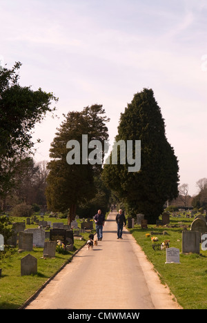 People walking their dogs along pathway at Ann's Hill Cemetery, Gosport, Hampshire, UK. - Stock Photo