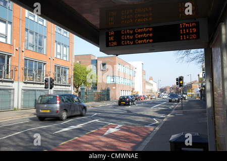 bus tracking system bustrak on a bus shelter stop on a main road in Belfast Northern Ireland uk - Stock Photo