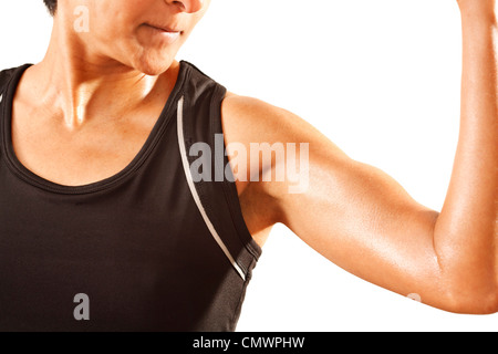 An athletic Asian Indian woman clenches her bicep. White background. - Stock Photo