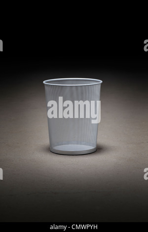 Empty wastepaper basket on dirty concrete floor. - Stock Photo