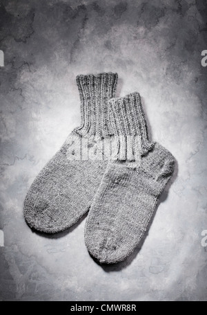 Hand-knitted grey wool socks on grey background - Stock Photo