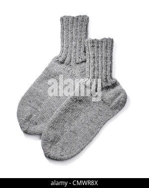 A Pair of hand-knit grey wool socks on white background with natural shadows. - Stock Photo