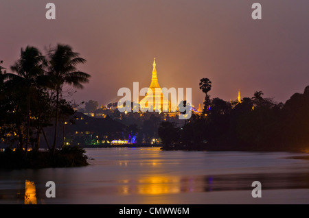 Illuminated Shwedagon Pagoda reflecting in the Kandawgyi Lake, Yangon, Myanmar - Stock Photo