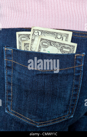 Photo of some US banknotes in the back pocket of a womans jeans. - Stock Photo