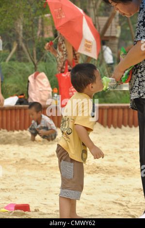 boy is drinking water in children's park in chongqing,china