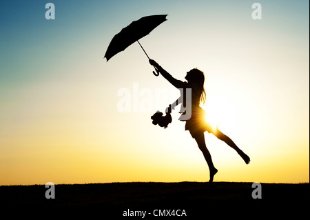 Young Girl jumping with an umbrella and teddy bear at sunset. Silhouette. UK - Stock Photo