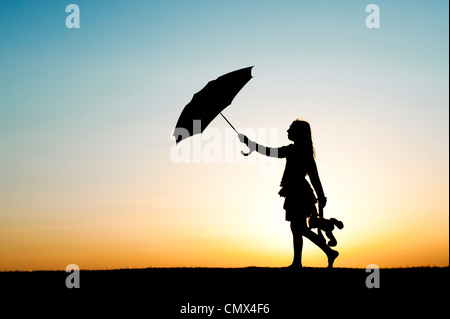 Young Girl walking with an umbrella and teddy bear at sunset. Silhouette.UK - Stock Photo