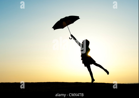 Young Girl jumping with an umbrella at sunset. Silhouette - Stock Photo