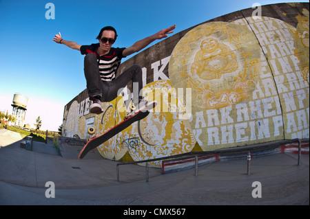 Germany, North Rhine-Westphalia, Duisburg, Skateboarder performing trick on ramp at skateboard park - Stock Photo