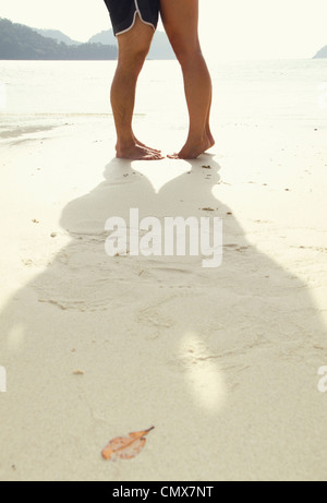 Thailand, Koh Surin, Young couple kissing on sandy beach - Stock Photo