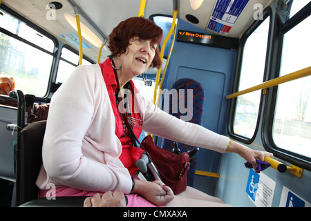 Woman in a wheelchair traveling by bus in London - Stock Photo