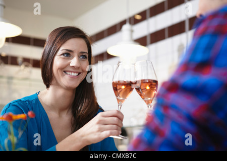 Germany, Cologne, Couple drinking wine, smiling - Stock Photo