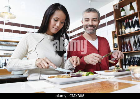 Germany, Cologne, Couple eating food in kitchen, smiling - Stock Photo