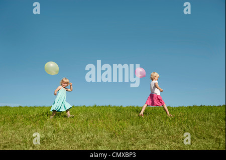 Germany, Bavaria, Girls walking in grass with balloons - Stock Photo