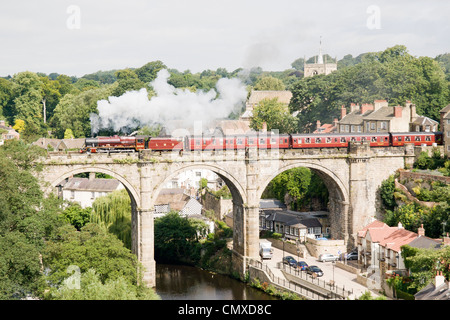 Steam locomotive pulling a passenger train on the mainline at Knaresborough - Stock Photo