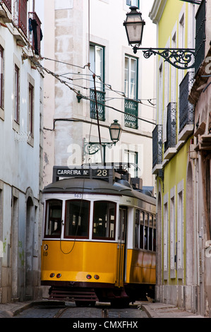 Electrico Tram 28 passing through a narrow street in Alfama district, Lisbon, Portugal - Stock Photo
