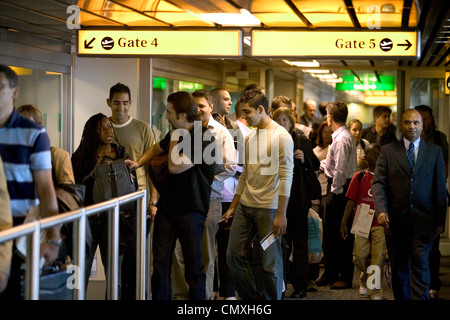 passengers queuing to board flights at heathrow airport - Stock Photo
